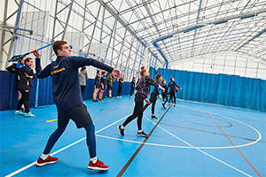 Blue flooring and blue curtains separating courts with student throwing javelins