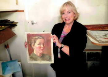 Jan Hodges holding artwork by Clarence Whaite