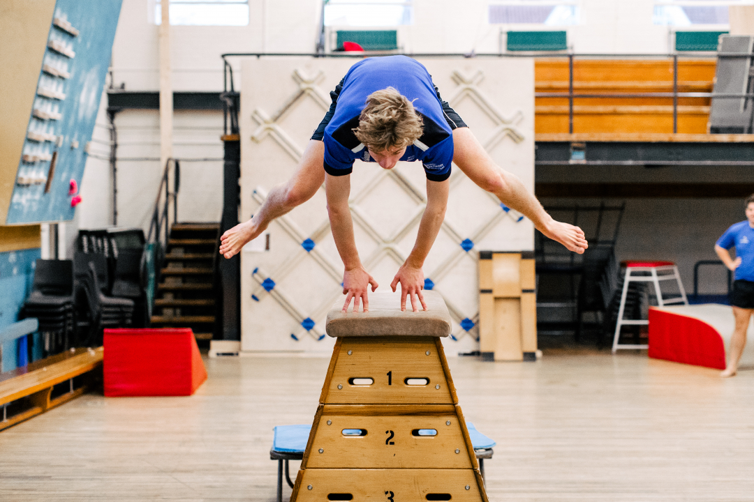 Boy vaulting over gymnastics box