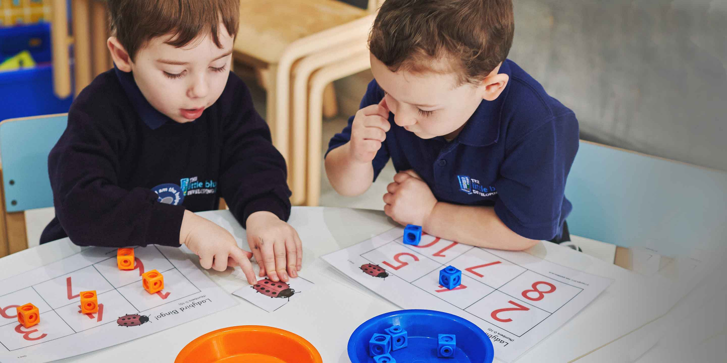 Two nursery children sat at a table playing a maths game