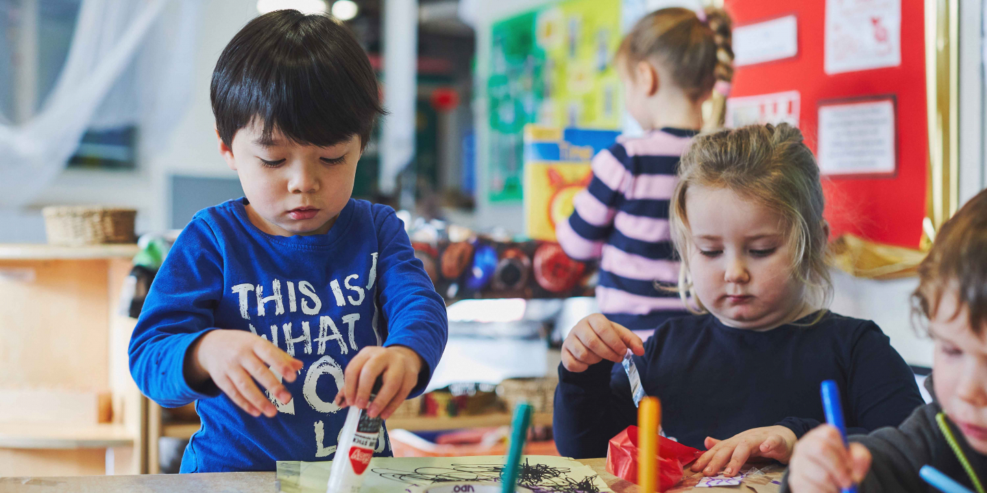 Young children colouring and playing in a nursery