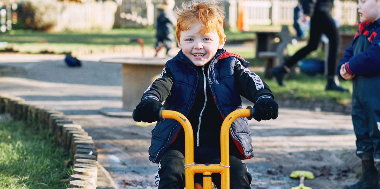A boy riding a yellow trike outdoors in a nursery garden
